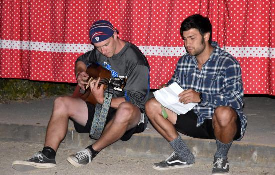 camp counselors performing at campfire