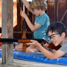 younger campers shoot air rifles at camp