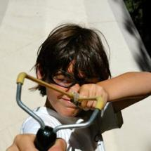 Boy shooting a sling shot at outdoor camp