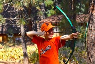 Boy shooting archery at outdoor camp